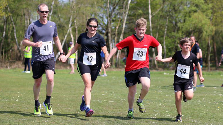 Left to Right: Paul (Teresa's Husband), Teresa and their 2 sons run with hands linked toward the camera at the Silchester Trail Family Fun Run in 2016