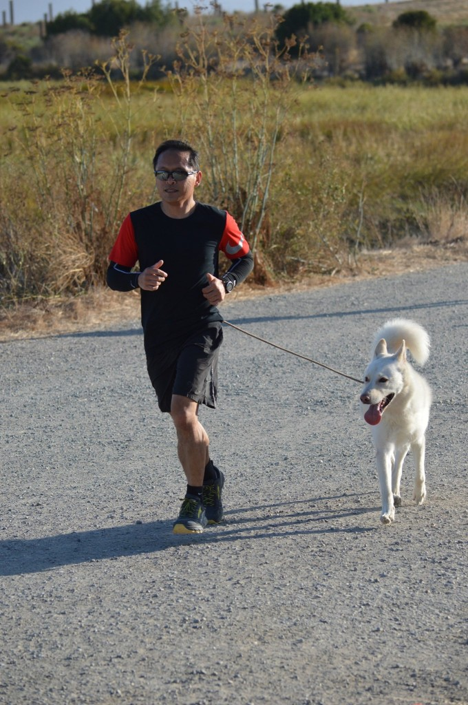 A runner and his white dog finish parkrun