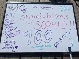 A whiteboard showing the words Congratulations Sophie 100 parkruns, surrounded by words of encourgement