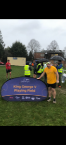 A man in an apricot parkrun shirt standing next to the purple KGVPF sign