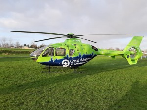 A green air ambulance helicopter landed on grass