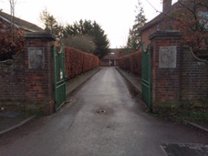A straight road running between green gates and brick gate posts with plaques
