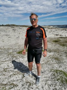Gerard Newman standing on the Cape Pembroke peninsula, wearing a Cape Wrath Challenge t-shirt and sunglasses