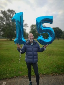 Paul Sinton-Hewitt holding balloons with the numbers 1 and 5