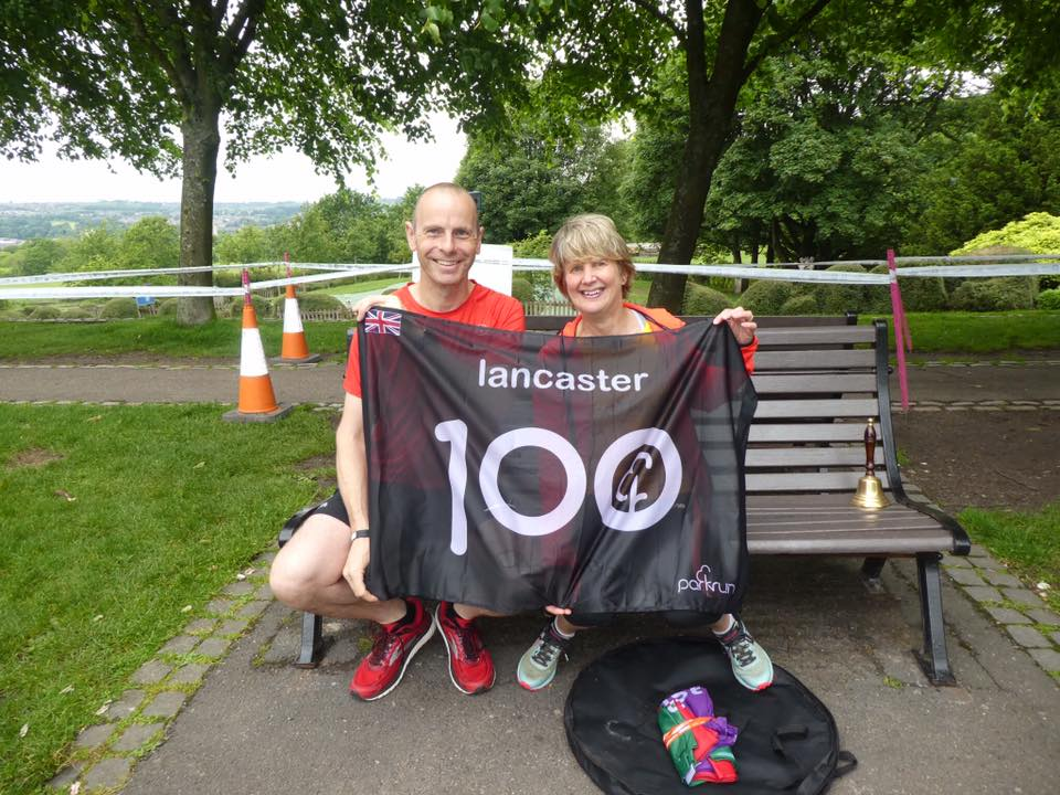 A man and woman sitting on a park bench celebrating completing 100 parkruns with a 100 parkruns flag.