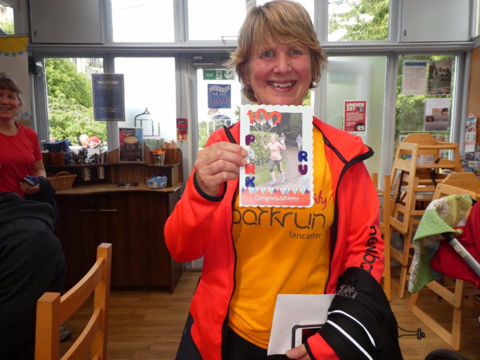 A woman shows a card celebrating completing 100 parkruns.