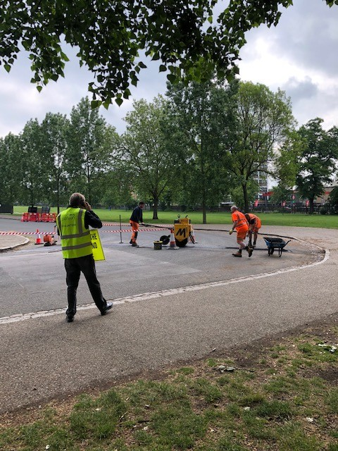 A wide carriageway is blocked by some hazard tape. Three workmen, with a wheelbarrow and another machine are laying tarmac across the carriageway. A parkrun volunteer is in the the corner of the photo, speaking on the telephone.