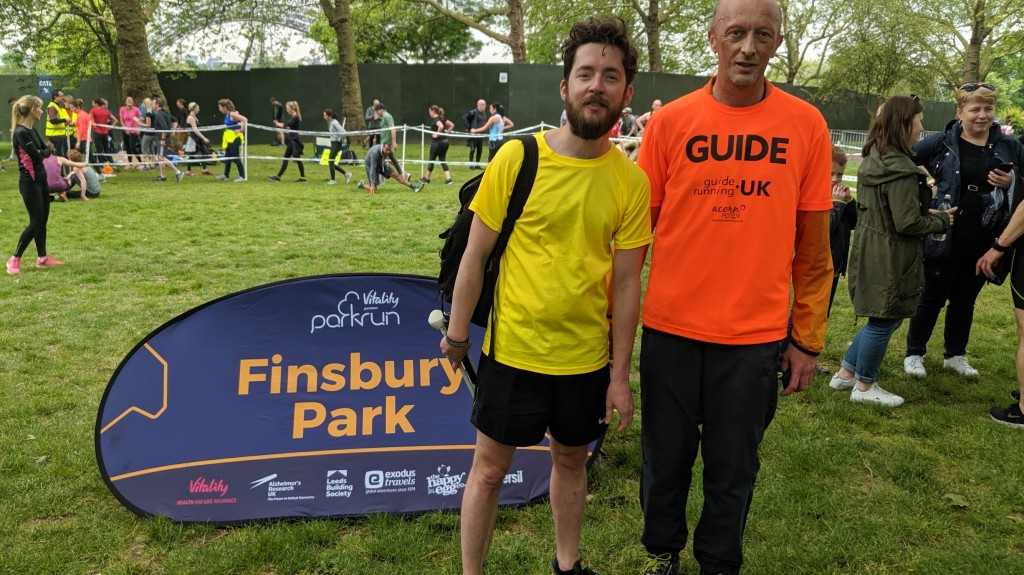 To the left, a pop-up sign for Finsbury parkrun. On the right, a runner in a yellow t-shirt stands next to another runner in an orange 'guide' t-shirt