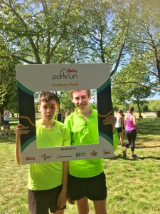 "Two teenage boys in matching bright yellow t-shirts stand inside a large branded ""Finsbury parkrun"" frame"